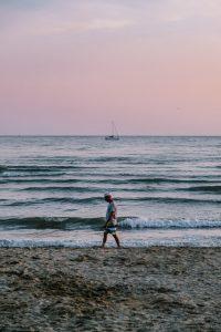 Single man walking on the beach